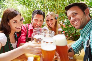 Freunde im Biergarten prosten sich mit Bier zu