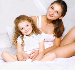 Lovely beautiful mom and daughter in bed