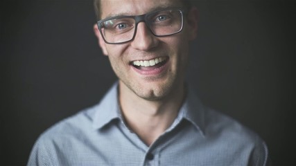 Young handsome man in glasses laughing in front of camera