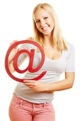 Frau hält at-Zeichen als Symbol für Internet