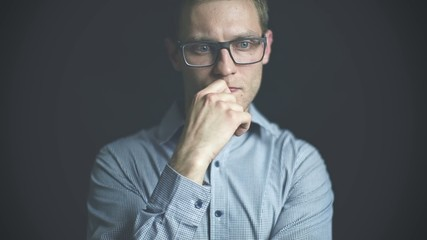 Close up of pensive man in glasses over black background.
