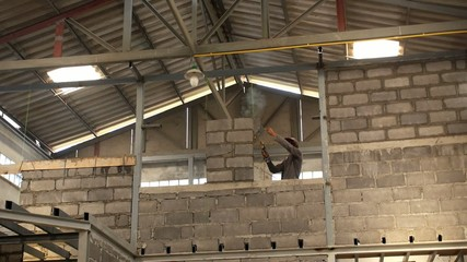 Asian Worker Welding Wall at Construction Area.