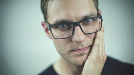 Handsome man in glasses touching his face over grey background