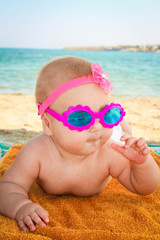 Beautiful little girl in sunglasses lies on the sea shore