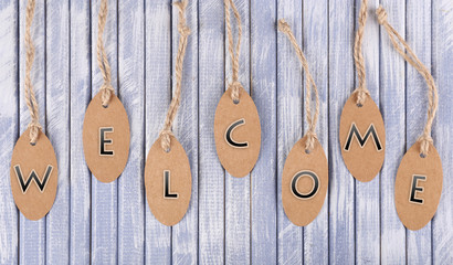 Welcome tags on wooden background