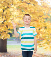 little boy in casual clothes making OK gesture
