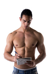Shirtless young man solving crosswords puzzles