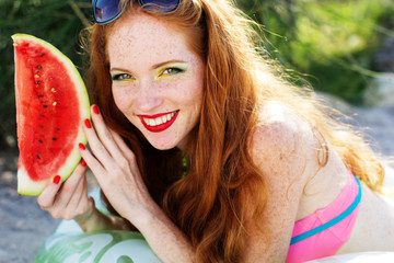 Smiling girl with freckles holding watermelon