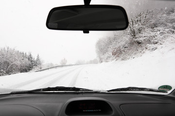 Driving a car on a snowy country road in winter