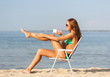 smiling young woman sunbathing in lounge on beach