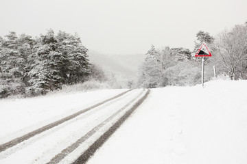 Snowy country road with traffic sign for downhill grade