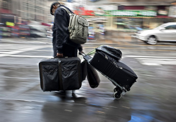 people with suitcases on a city street