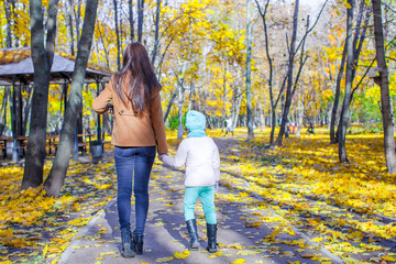 Young mother and her adorable daughter walking in yellow autumn