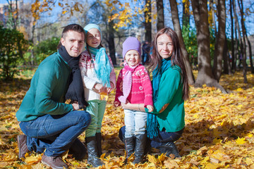 Young family with cute little girls in autumn park on sunny day