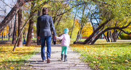 Young father and little girl walking in autumn park
