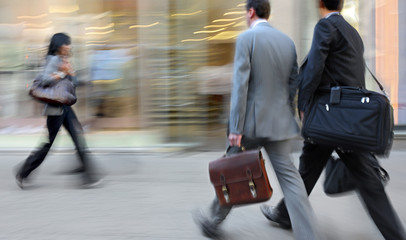 motion blurred business people walking on the street