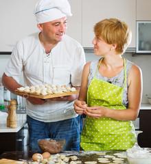 Happy couple cooking  russian dumplings (pelmeni)