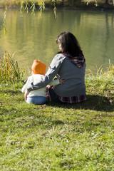 Ребёнок и мама обнимаются на берегу озера