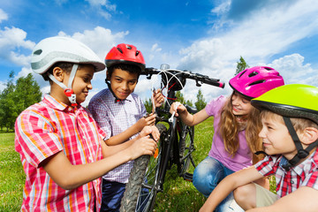 Smiling kids in helmets repair bike together