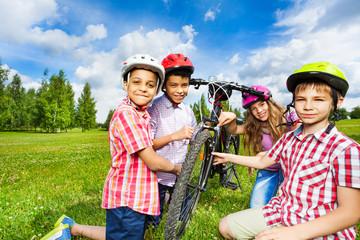 Happy children in colorful helmets repair bicycle