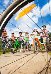 Kids with helmets hold bikes view through spoke