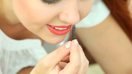 Woman applying makeup on beach