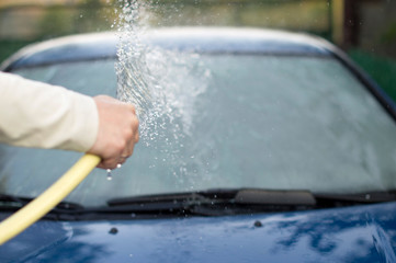 The process of washing cars with a hose with water