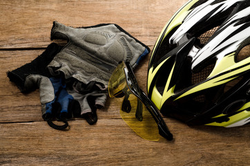 Helmet, gloves and water bottle - bicycle accessories on Wood.