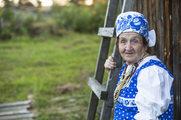Old woman in ethnic clothes, outdoors.