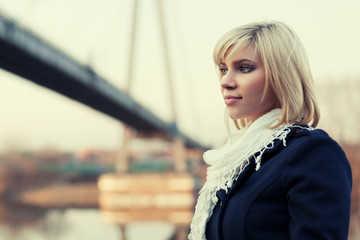 Young blond fashion woman at the river bridge
