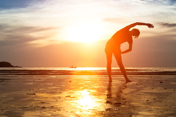 Silhouette of girl practicing yoga at sunset.