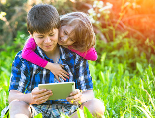 Young boy with a tablet PC and his little sister.