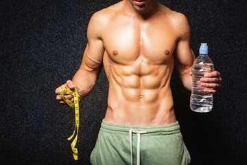 Shirtless bodybuilder holding water bottle and tape measure