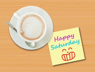 "Coffee cup on wood table with paper note ""Happy Saturday"""