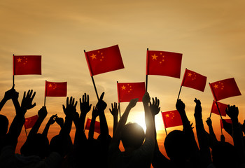 Group of People Waving Chinese Flags in Back Lit