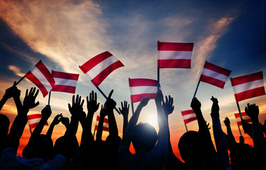 Silhouettes of People Holding Flag of Austria
