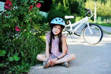 Kid girl  in blue halmet with bicycle