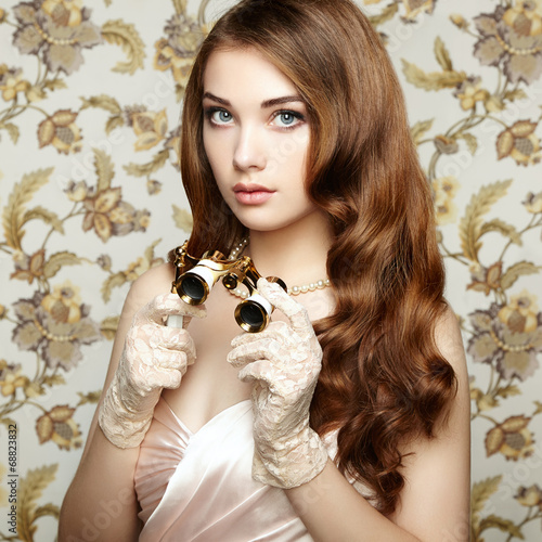 Portrait of young woman with binoculars. Fashion portrait