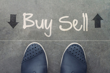 Hand drawn BUY or SELL design word on front of business man feet