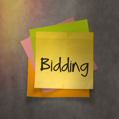 """""""bidding"""" text on sticky note paper on wall texture"""
