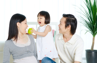 Lovely asian child feeding her mother with apple