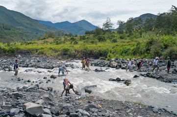 People crossing river at valley of  river Baliem at island New G