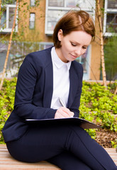 a business woman writting on a clipboard.