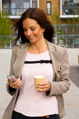 young woman holding a coffee and phone.