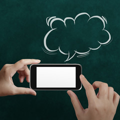 hand using mobile phone with speech bubble on chalkboard