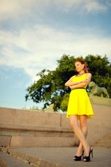 Beautiful woman in yellow dress on in Sankt Petersburg at sunset