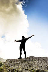 man standing on top of a cliff with arms raised