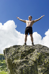 Young man standing on top of a cliff with arms raised