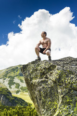 Young man standing on top of a cliff