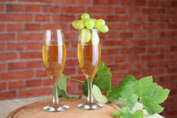 Grapes and two glasses of the white wine. Red brick